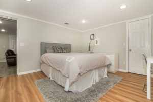 Picture of bed with gray bedspread and gray rug and hardwood floors