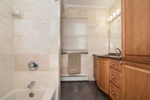 Travertine Bathroom with wood cabinets and stainless faucet